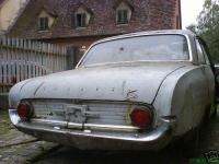 Altes Auto hinter altem Haus
